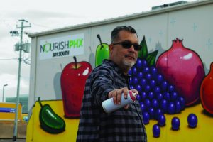 Lalo Cota in front of Mural at Nourish PHX